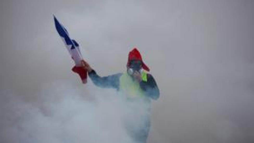 A demonstrator holds a French flag as he walks amid the tear gas during a protest of Yellow vests (Gilets jaunes) against rising oil prices and living costs, on December 1, 2018 in Paris