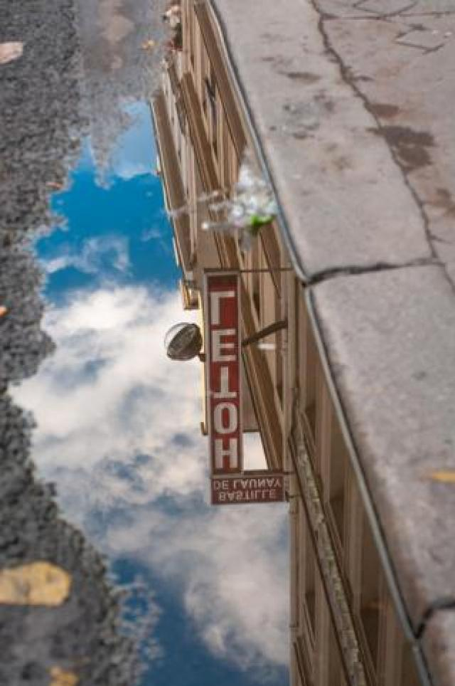 Hotel sign reflected in a puddle