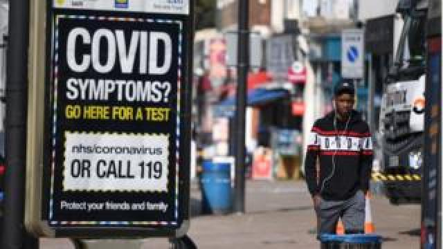 Pedestrians walk past a sign displaying a Covid helpline in London, Britain, 15 September 2020
