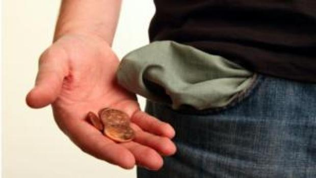 Close up man's hand with turned out pocket and coins