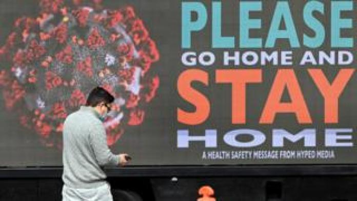 A man wearing a mask walks past a billboard in Melbourne which reads: Please go home and stay home