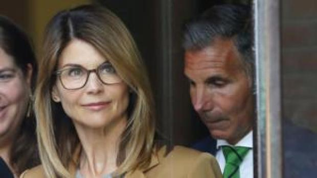 US actress Lori Loughlin (L) and husband Mossimo Giannulli (R) leave court in Boston, Massachusetts, on 3 April 2019