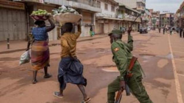 Security: A police officer beats a female orange vendor on a street in Kampala, Uganda, on March 26, 2020, after Ugandan President Yoweri Museveni directed the public to stay home for 32 days