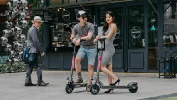 Two people on scooters in front of a cafe
