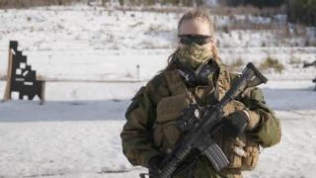 Jannike holding a gun and looking at the camera. She wears sunglasses and a mask covers her nose and mouth
