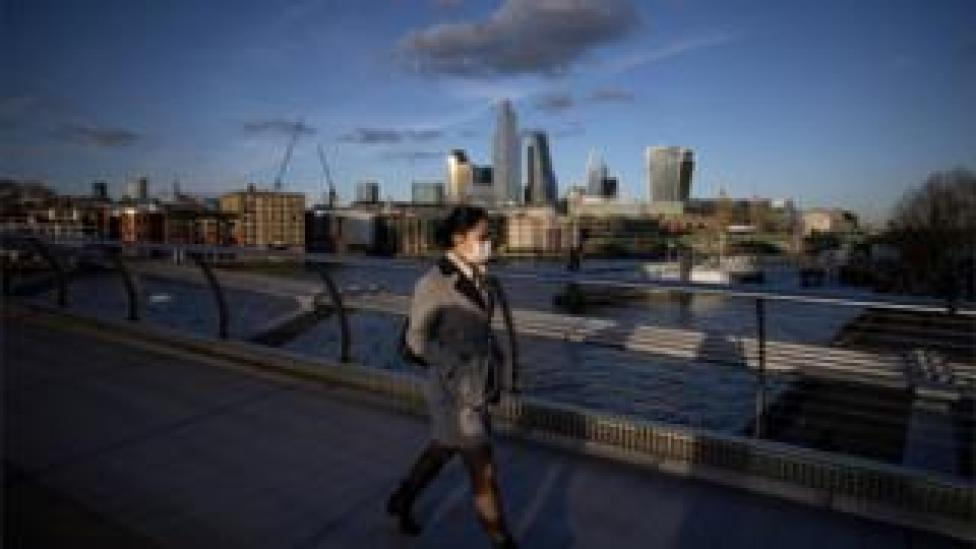 Woman wearing a mask walking on a bridge over the Thames
