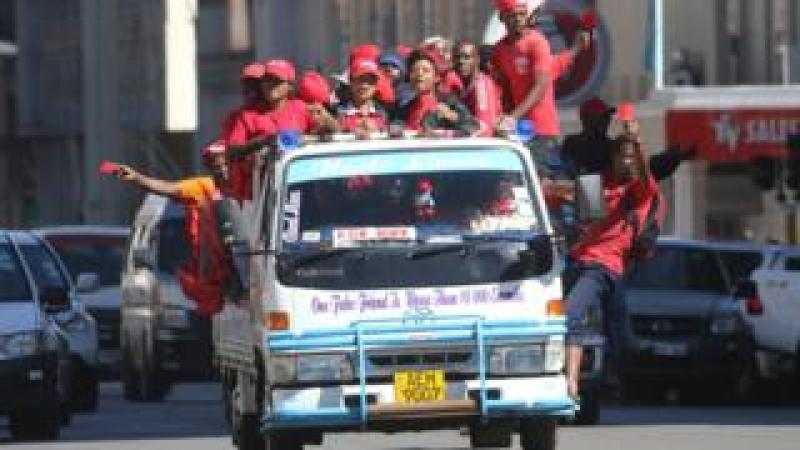 MDC supporters dressed in red hang from a vehicle during a protest in Harare, Zimbabwe - Wednesday 11 July 2018