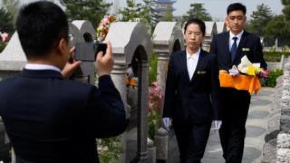 Staff film a tomb sweeping ceremony for a customer