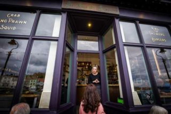 A staff member tells people that the bar is full at The Moon and Sixpence, Whitby