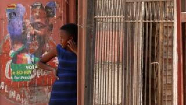 A girl looks on next to a defaced campaign poster of President Emmerson Mnangagwa in Harare, Zimbabwe - Monday 6 August 2018