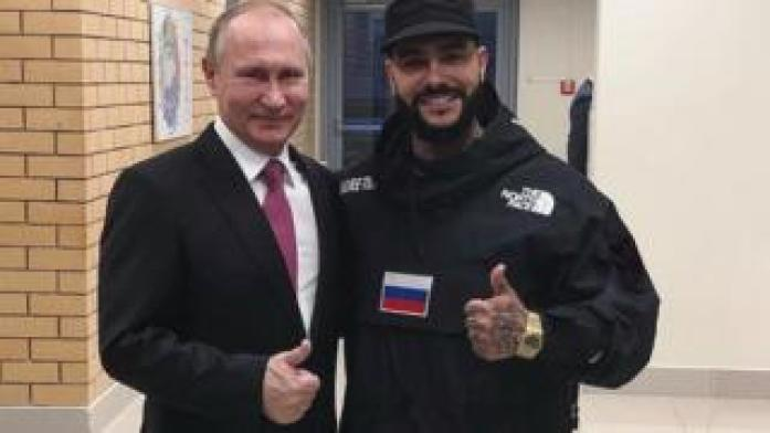 Vladimir Putin and Timati stand side-by-side, giving the thumbs-up gesture