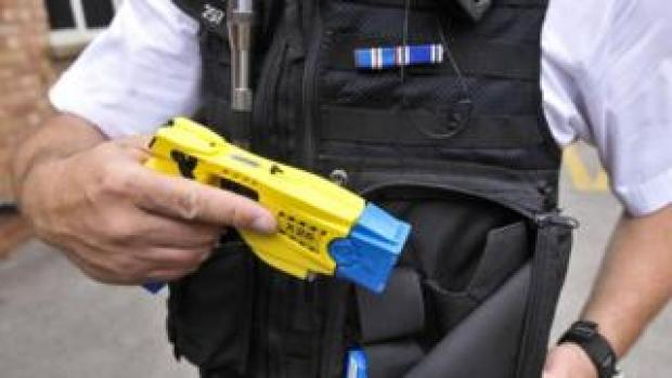 A police officer holds a Taser