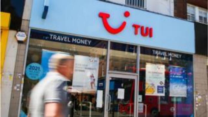 man walks past Tui shop