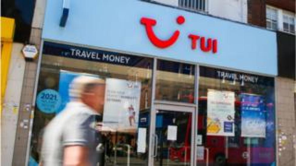 man walks past Tui shop