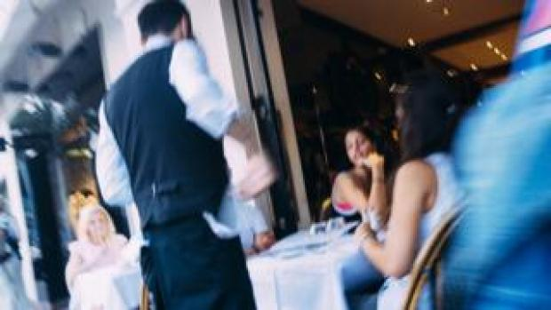 A waiter serves diners