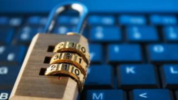 This stock image shows a padlock lying on top of a laptop's keyboard