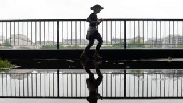 A woman runs through a puddle on the South Bank in London