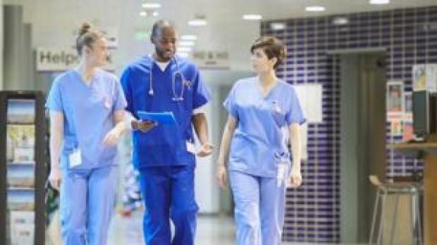 Three doctors walking down corridor