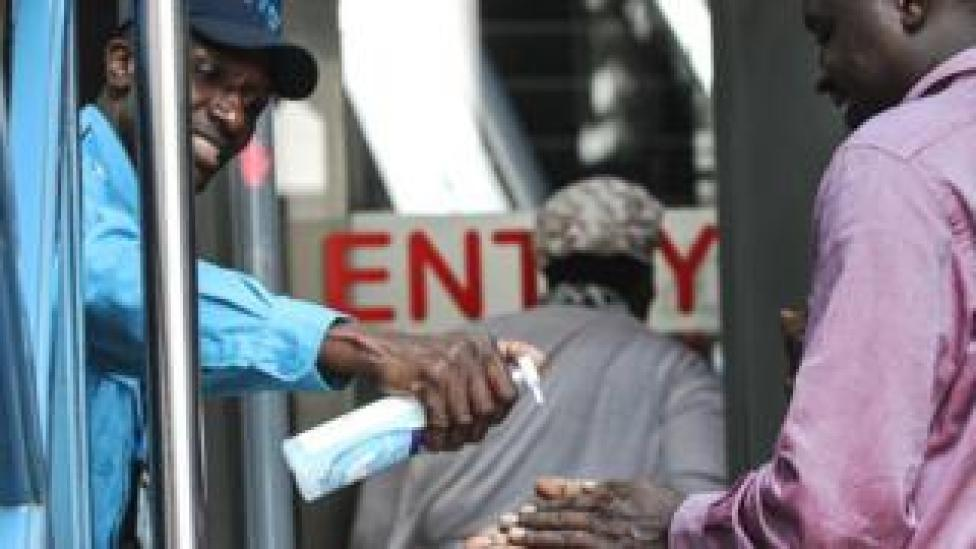 A security guard gives hand disinfectant to visitors as precaution measures at an entrance of building in Nairobi, Kenya - 13 March 2020