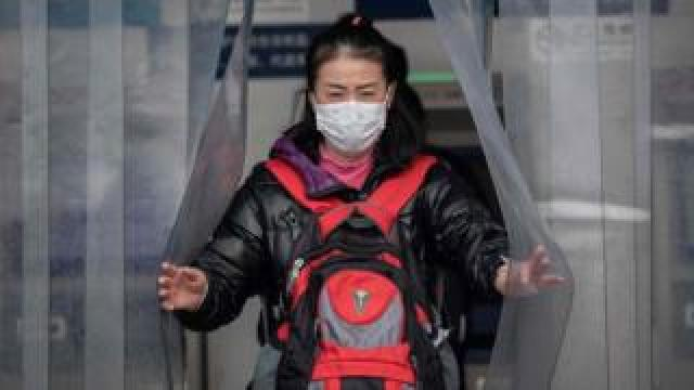 Woman wearing a protective facemask at the Beijing railway station