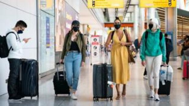Three women in masks arriving at Heathrow