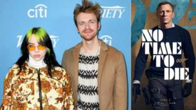 Billie Eilish and Finneas O'Connell with the poster for No Time To Die