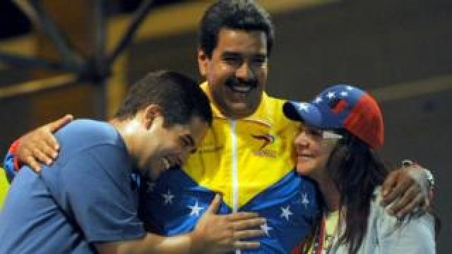 President Nicolas Maduro embraces his wife Cilia Flores and son Nicolas Maduro during a 2013 campaign rally