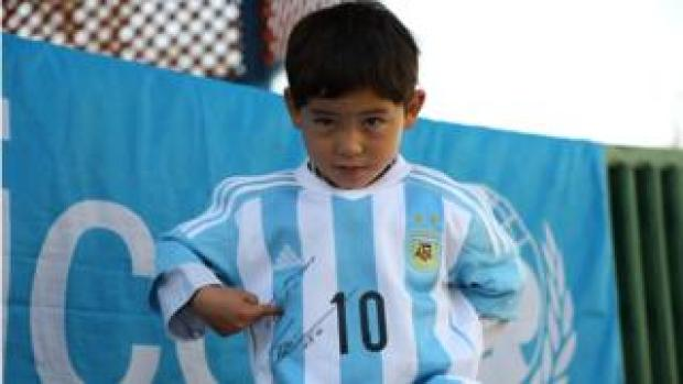 Afghan boy Murtaza Ahmadi posing with a jersey sent to him by Argentine football star Lionel Messi in 2016