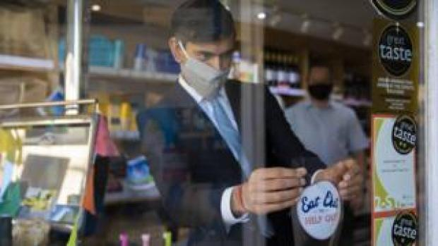 "The Chancellor Rishi Sunak applies an ""eat out to help out"" sticker in a window"