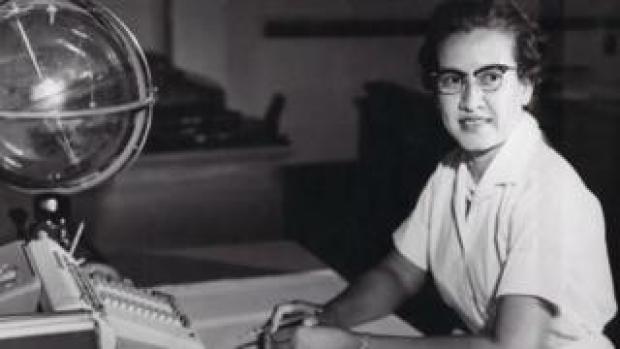 Katherine Johnson sits with a globe