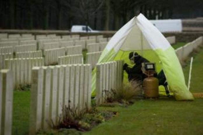 Person covered by a small tent repairing a gravestone at Delville Wood Cemetery in France