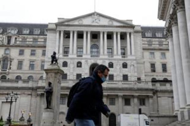 A man walks past the Bank of England in London