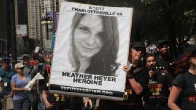 A demonstrator carries a sign remembering Heather Heyer during a protest on August 13, 2017 in Chicago, Illinois