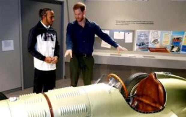 Prince Harry and Formula One world champion driver Lewis Hamilton look at a car