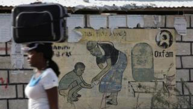 A woman walks carrying a suitcase on her head next to an Oxfam sign on the outskirts of Port-au-Prince, Haiti