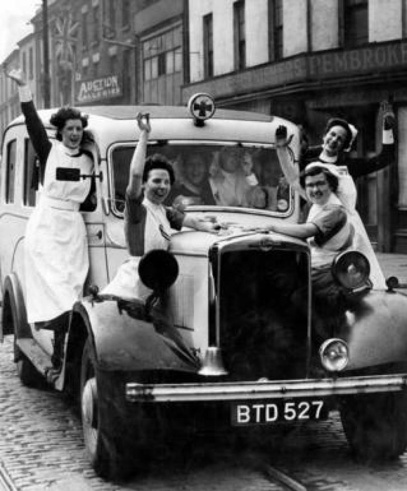 Nurses drive a car waving