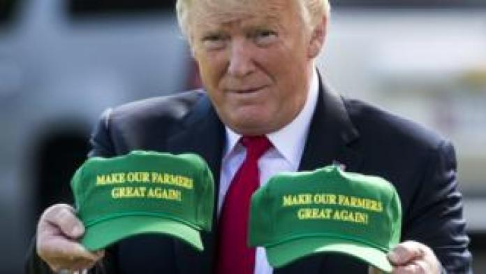 """US President Donald Trump displays hats that read: """"Make Our Farmers Great Again!"""" at the White House, Washington DC, 30 August 2018"""