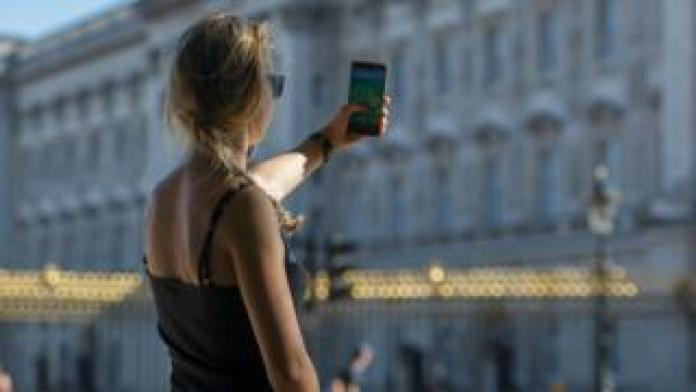 A woman is seen playing Pokémon Go on her phone next to Buckingham Palace in London