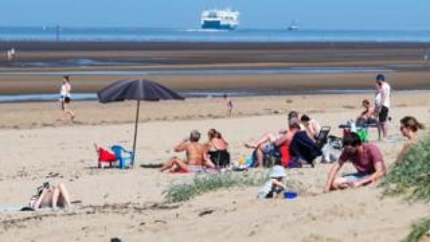People relax on Crosby Beach on the Merseyside