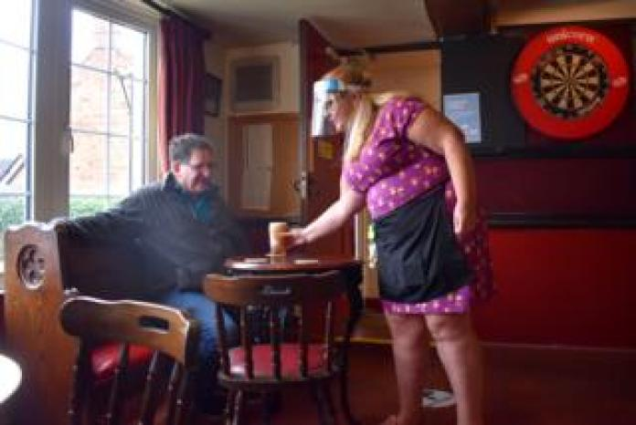 Woman serving pint to customer in pub