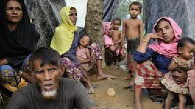 Rohingya women sit in front of their makeshift shelters in a camp in Ukhiya, Cox's Bazar, Bangladesh, 11 September 2017