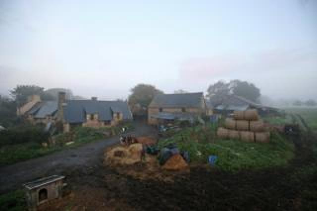 A view of Jean-Bernard's farm including several buildings and farm animals