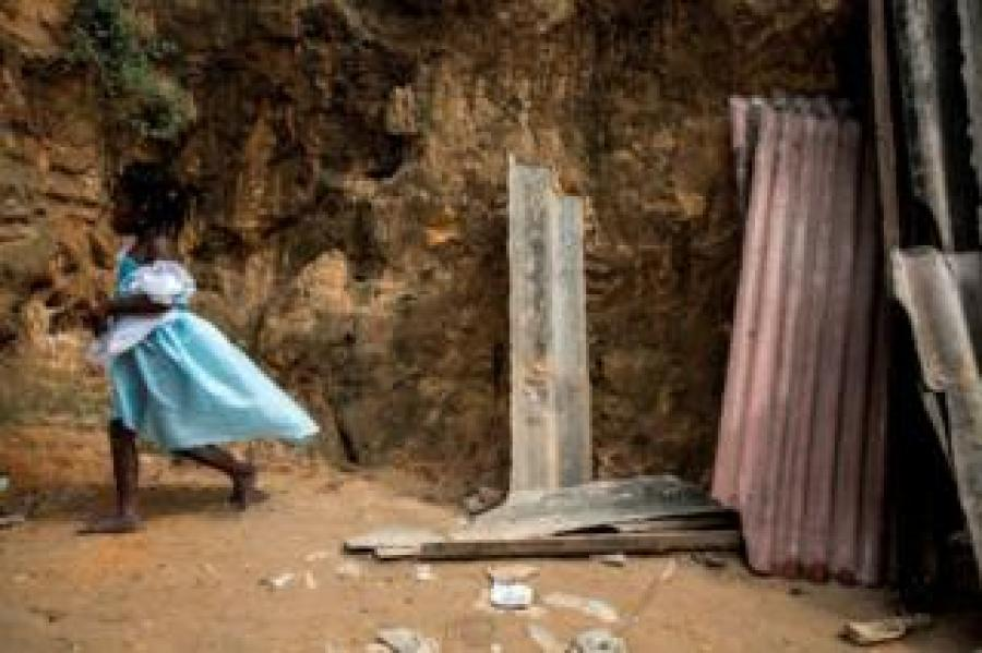 A child walks past the remains of a landslide in Ngaliema district on January 5, 2018 in Kinshasa. Thirty-seven people died overnight when torrential rain and mudslides swept though shanty homes in Kinshasa.