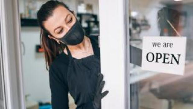 A woman in a face mask next to a sign on a shop door reading 'open'