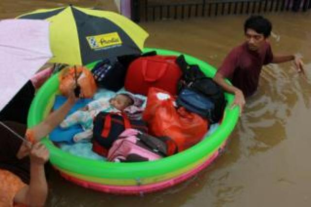 A baby is rescued in an inflatable boat after floods hit a residential area in Tangerang, near Jakarta, Indonesia, 1 January 2020.
