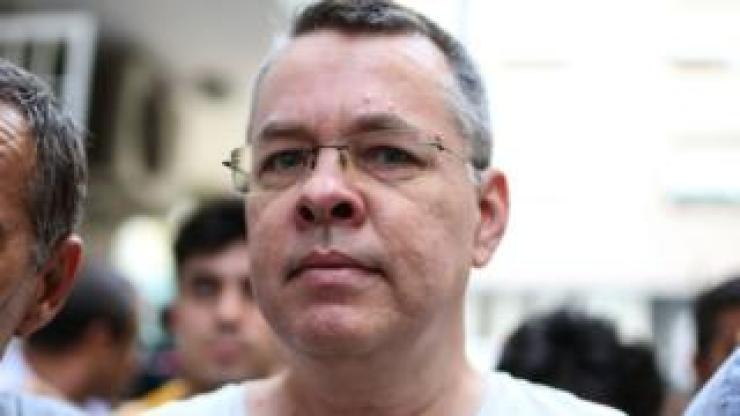Andrew Brunson escorted by Turkish plain clothes police officers arrives at his house on July 25, 2018 in Izmir.