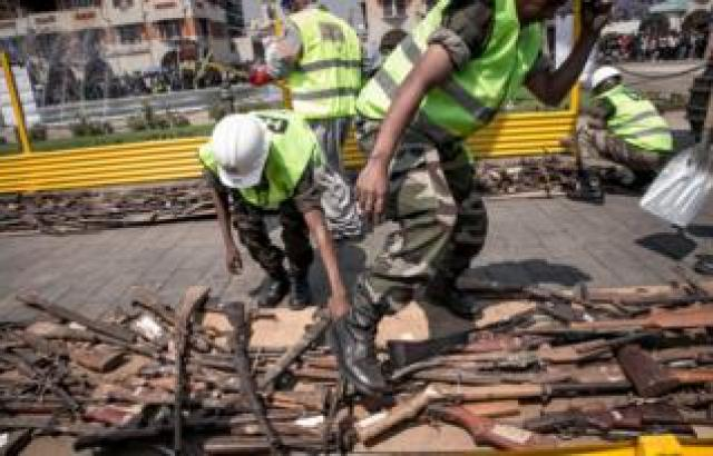 "Malagasy army personnel inspect firearms that are being destroyed by a bulldozer during a ceremony organised by the government to disable approximately 800 weapons, on October 16, 2018, on Antananarivo""s May 13th Square. - These weapons are mainly handmade hunting rifles and assault rifles from abroad."