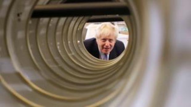 Boris Johnson looking down tube in factory