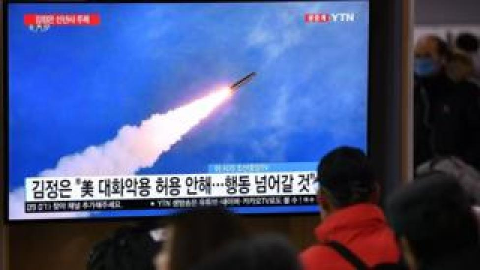 trump People watch a television news programme showing file footage of North Korea's missile test,