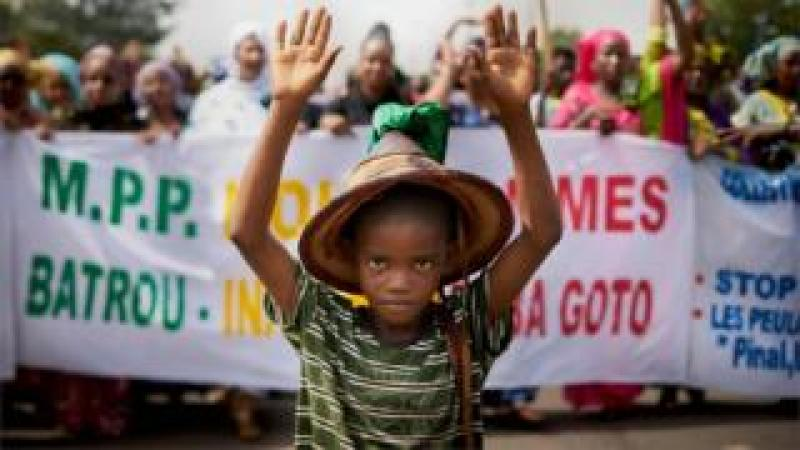 """A Fulani boy protests in front of a sign saying """"Stop the Genocide"""" during a silent march orhanized by the Mouvement Peul et allies pour la paix, an organisation of ethnic Fulani people on June 30, 2018 in Bamako in response to a massacre in Koumaga, Mali. On June 23, at least 300 Christian farmers were killed and ten are missing following an attack in central Mali, believed to have been carried out by Muslim Fulani hunters"""
